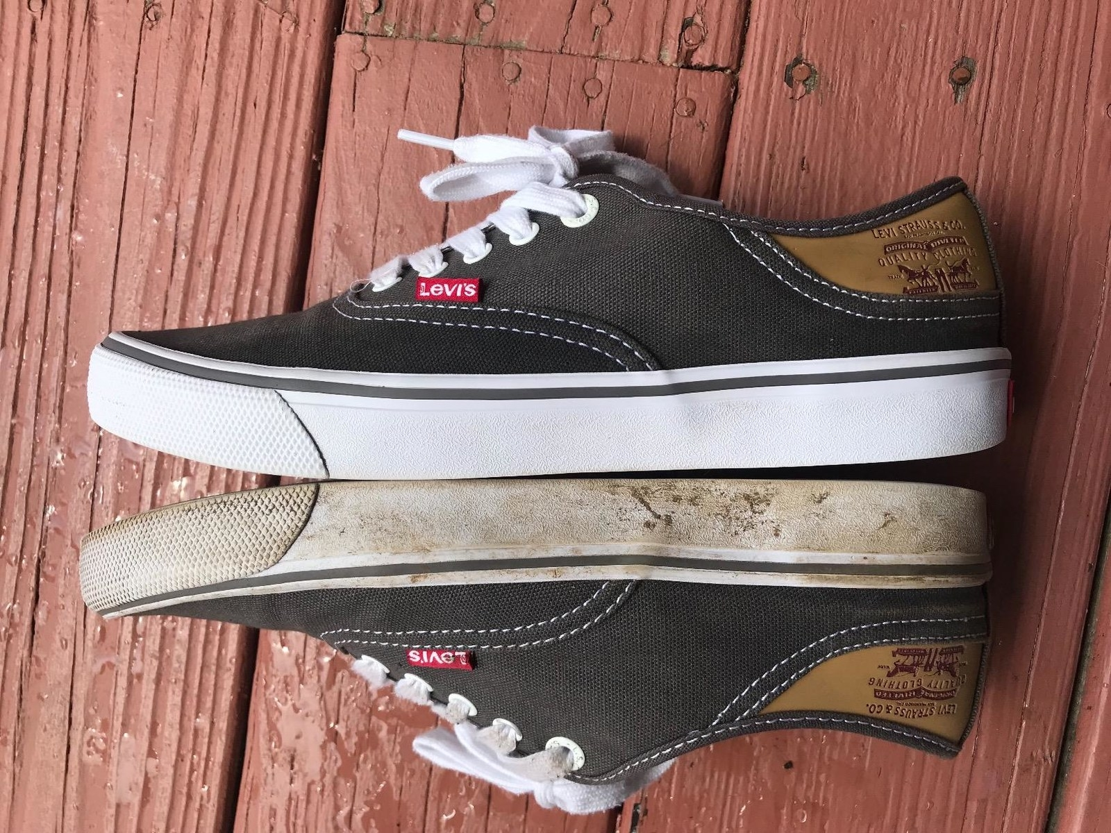 A reviewer's pair of canvas, rubber-bottom sneakers: one crusted and stained with dirt all over; the other clean, so the rubber and laces are white and the rest of the shoe is a pure black