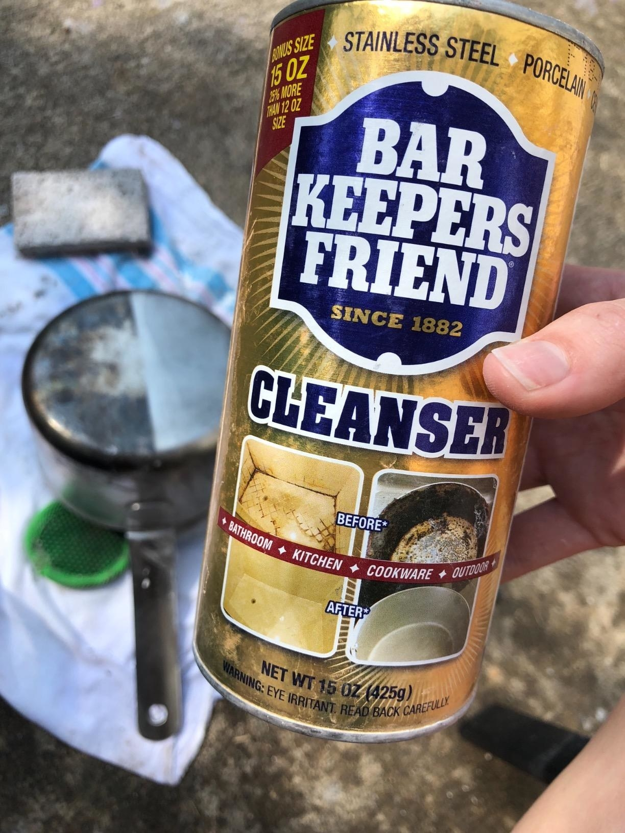 the can of cleanser held by reviewer in front of pan that is half cleaned to show how effective it is
