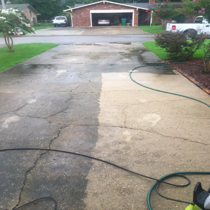 reviewer image of a driveway half cleaned with the sun joe pressure washer; the left side is dark and dirty, and the right side is clean and beige