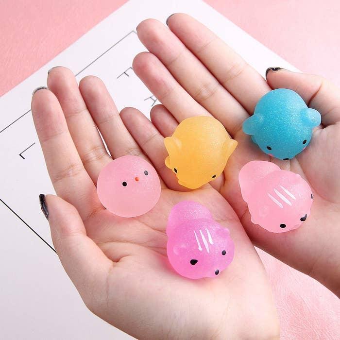 hand holds blobby looking squishy animals