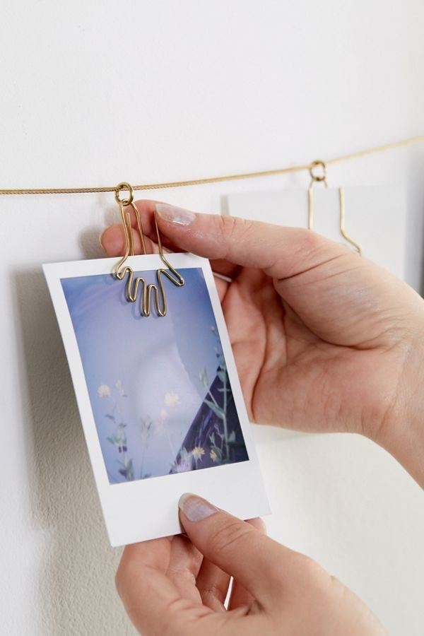 model clips polaroid into hand-shaped clip on clothesline