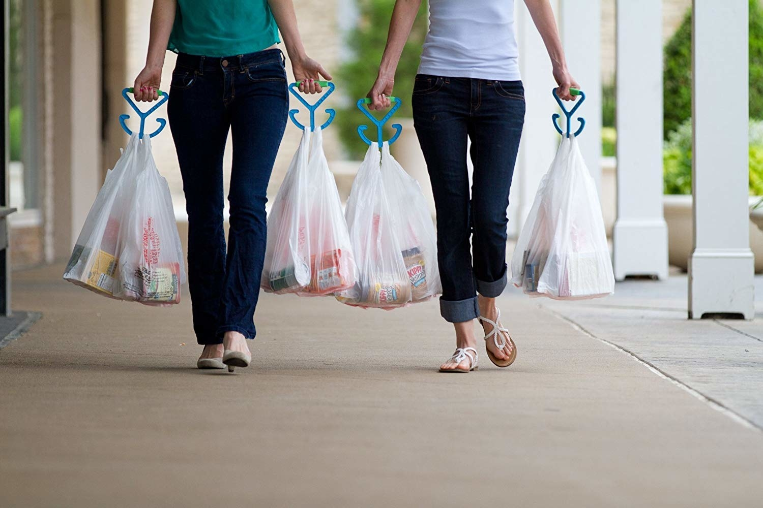 Two people carrying several bags in each hand hung on the blue handles