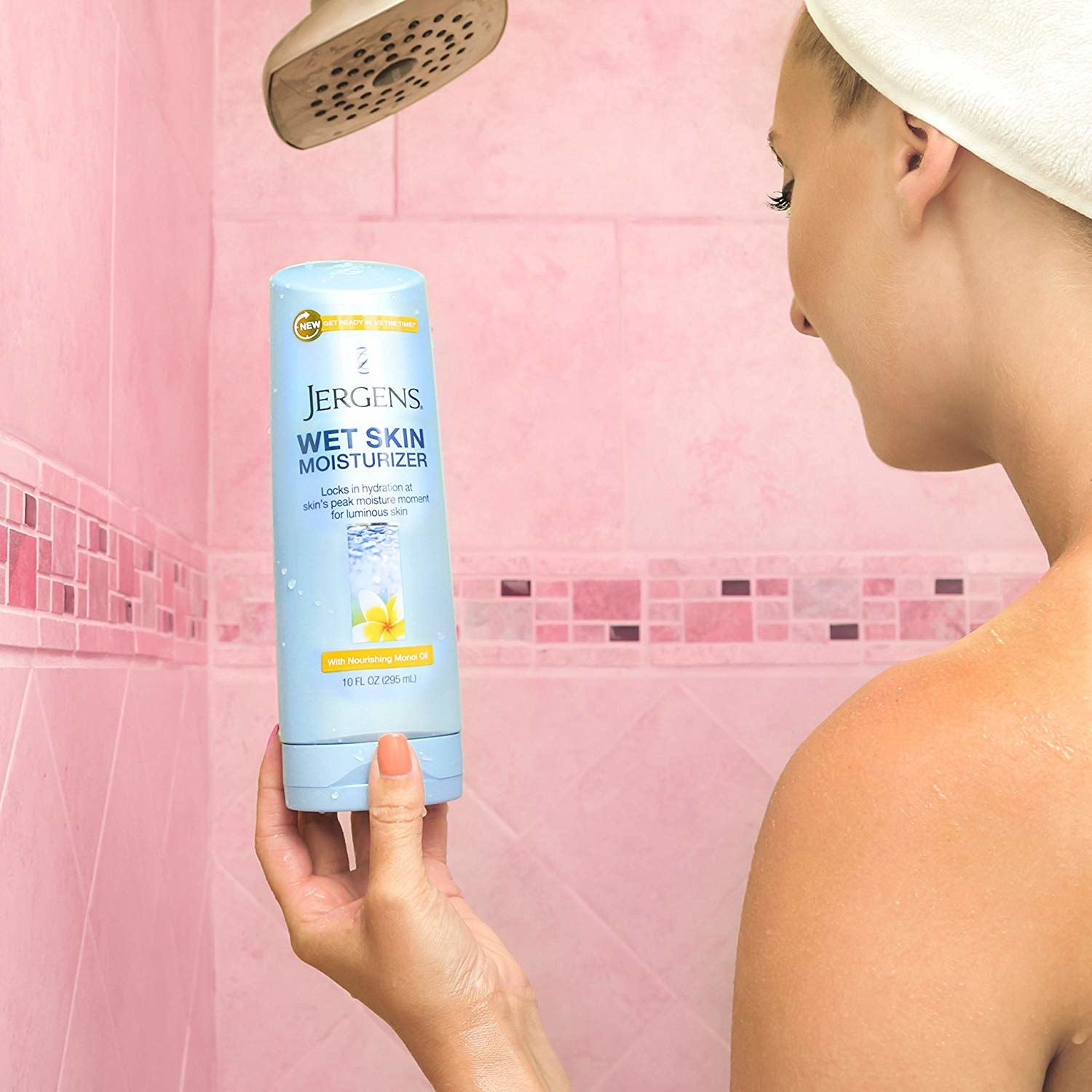 Model holding the bottle of lotion in the shower