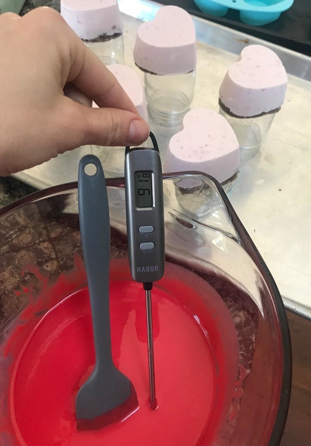 Reviewer using the thermometer, which features a digital display, to measure the temperature of a mixture