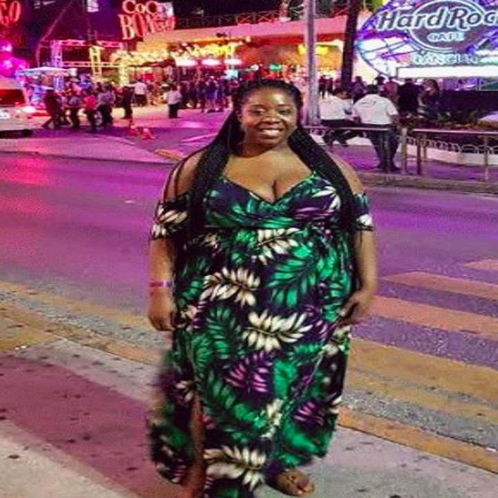 A reviewer wearing the dress in a black, white, green, and purple leaf print