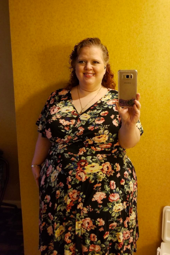 A reviewer wearing the short-sleeve dress in black with a floral print