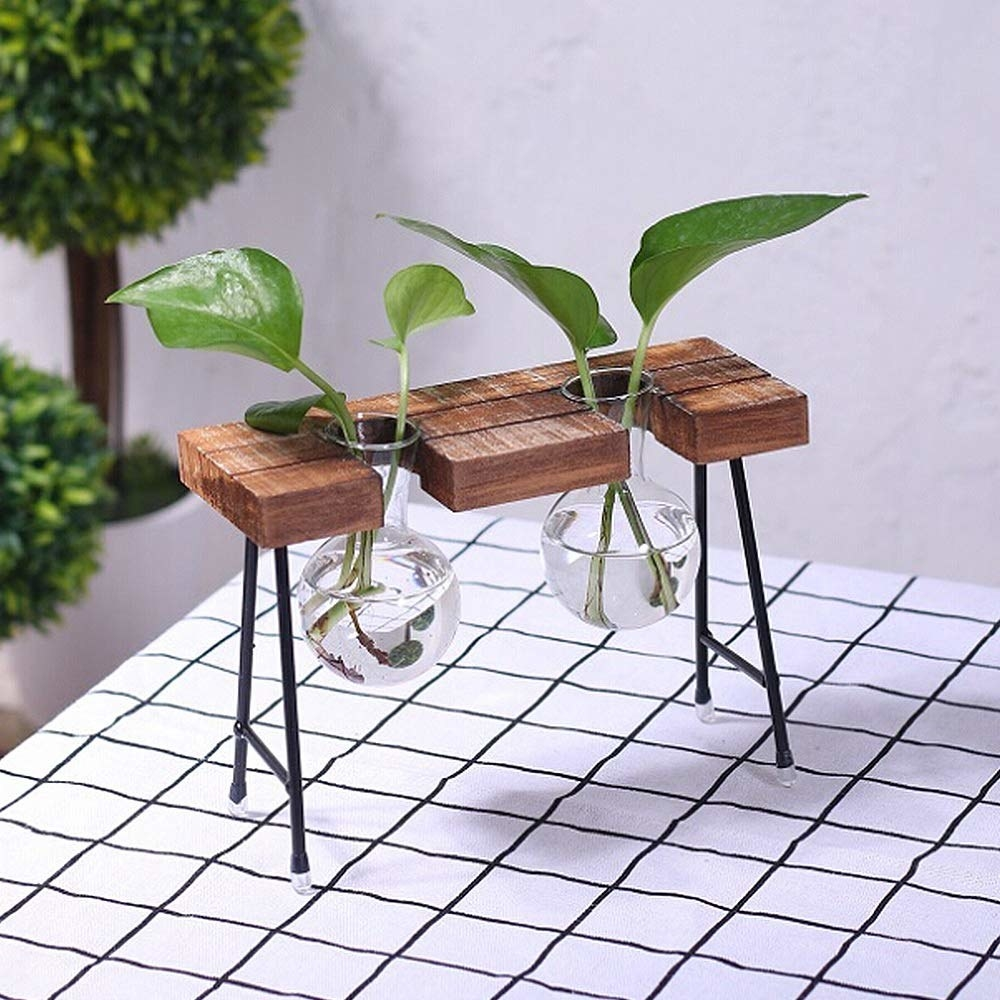 two round bud vases held upright with wooden shelf with thin metal legs