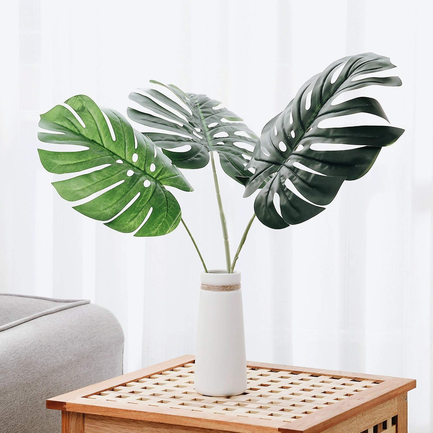 three large plastic monstera leaves in a vase