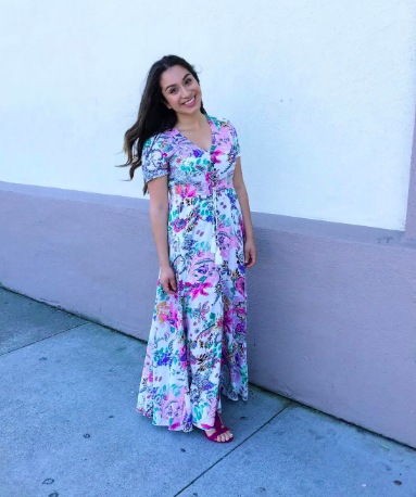 A reviewer in the short-sleeved dress in white with a pink, blue, and teal print