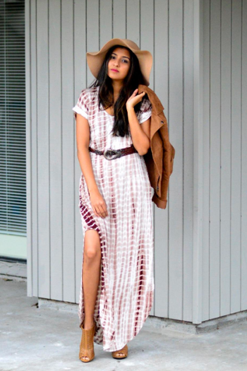 A reviewer wearing the brown and white dress with a belt and floppy hat, and sticking their leg through the high slit