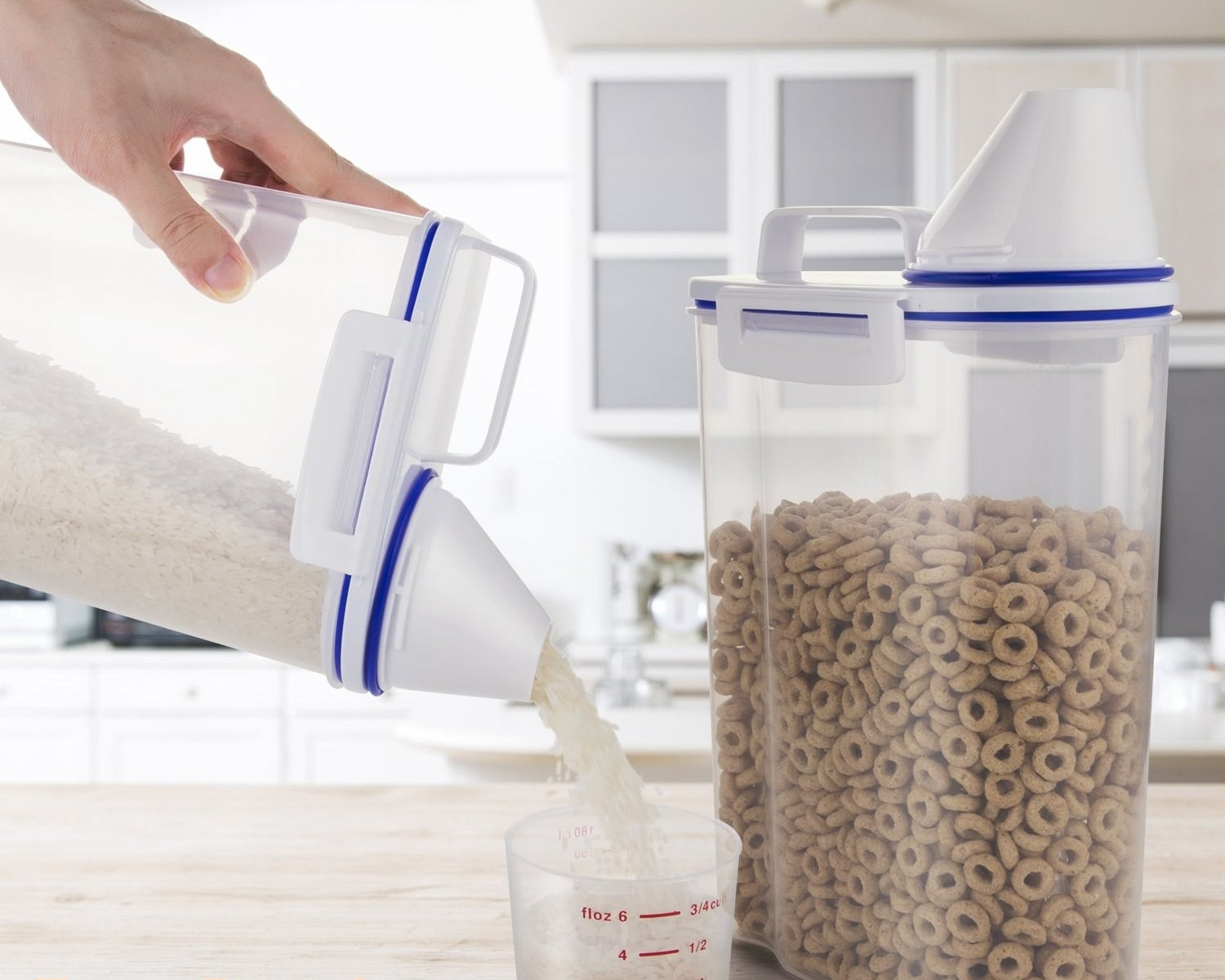 A hand pours rice out of the rectangular, handled container into a measuring cup, with another container containing cheerios in the background