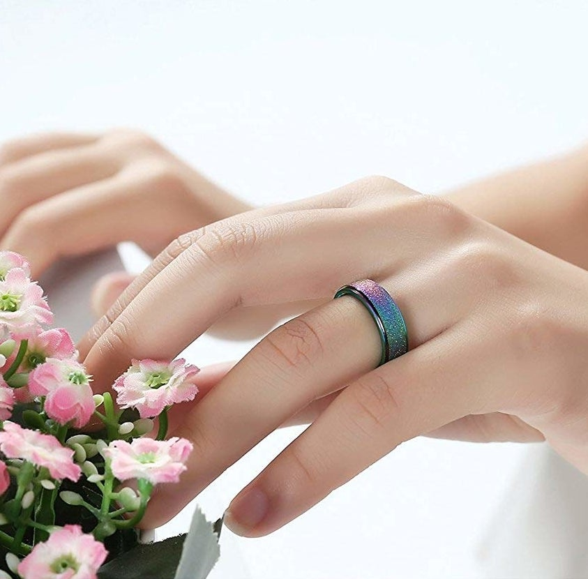 Hand wearing the ring in the color rainbow
