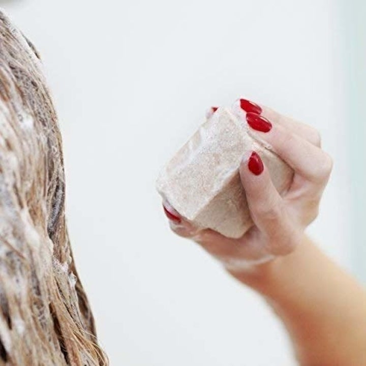 hand holding bar of soap and hair lathered with soap suds