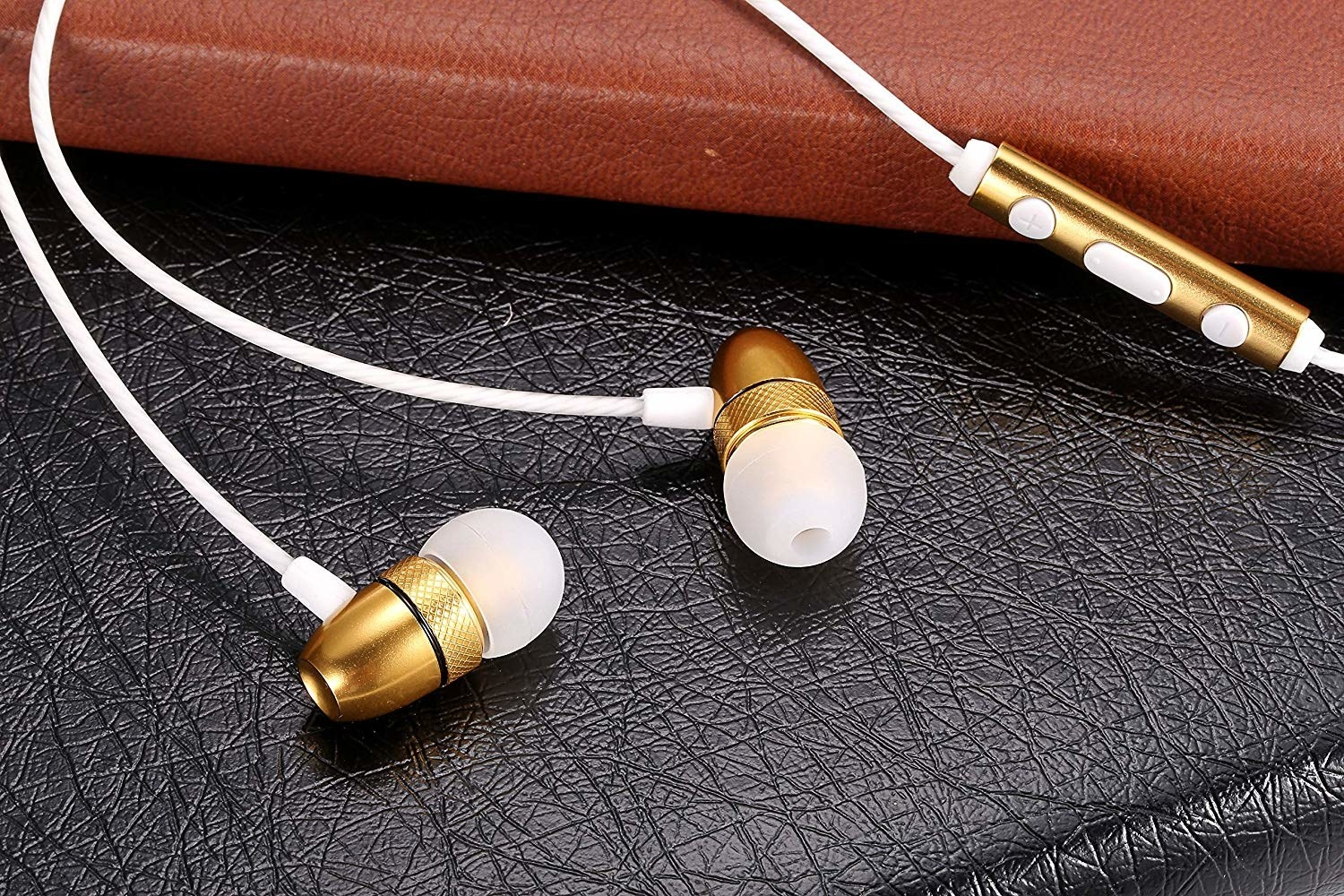 The earbuds, featuring white ear tips and cord with gold accents