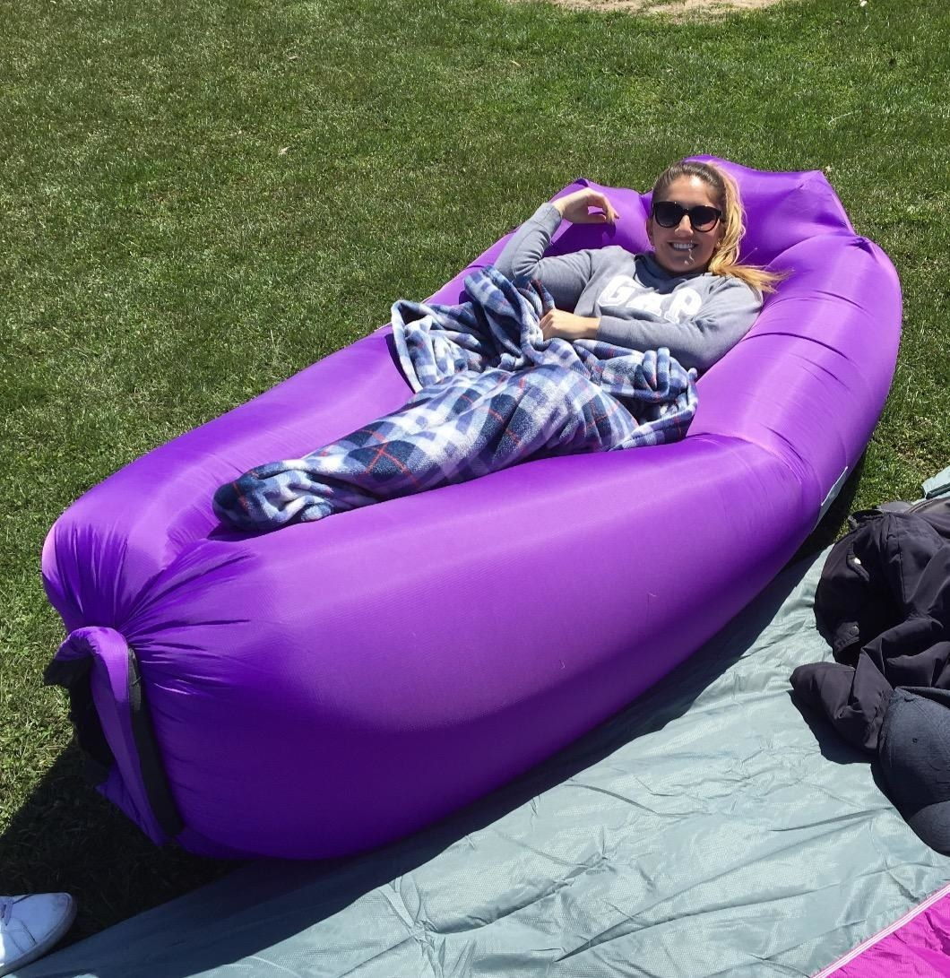 reviewer laying in purple inflated chair