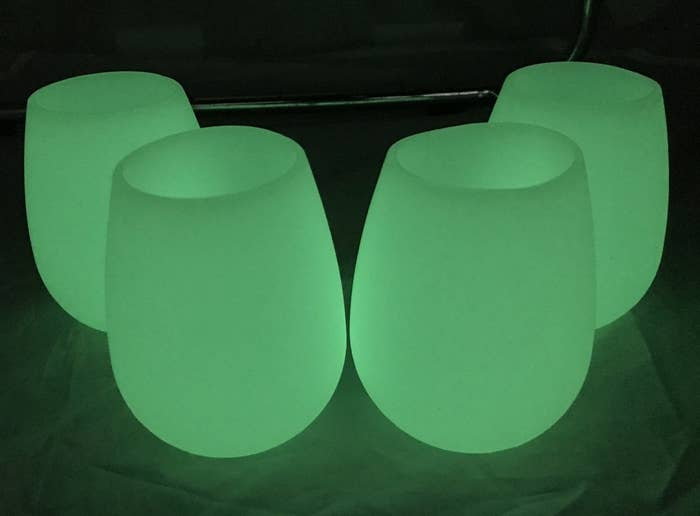 four stemless wineglasses glowing green in the dark