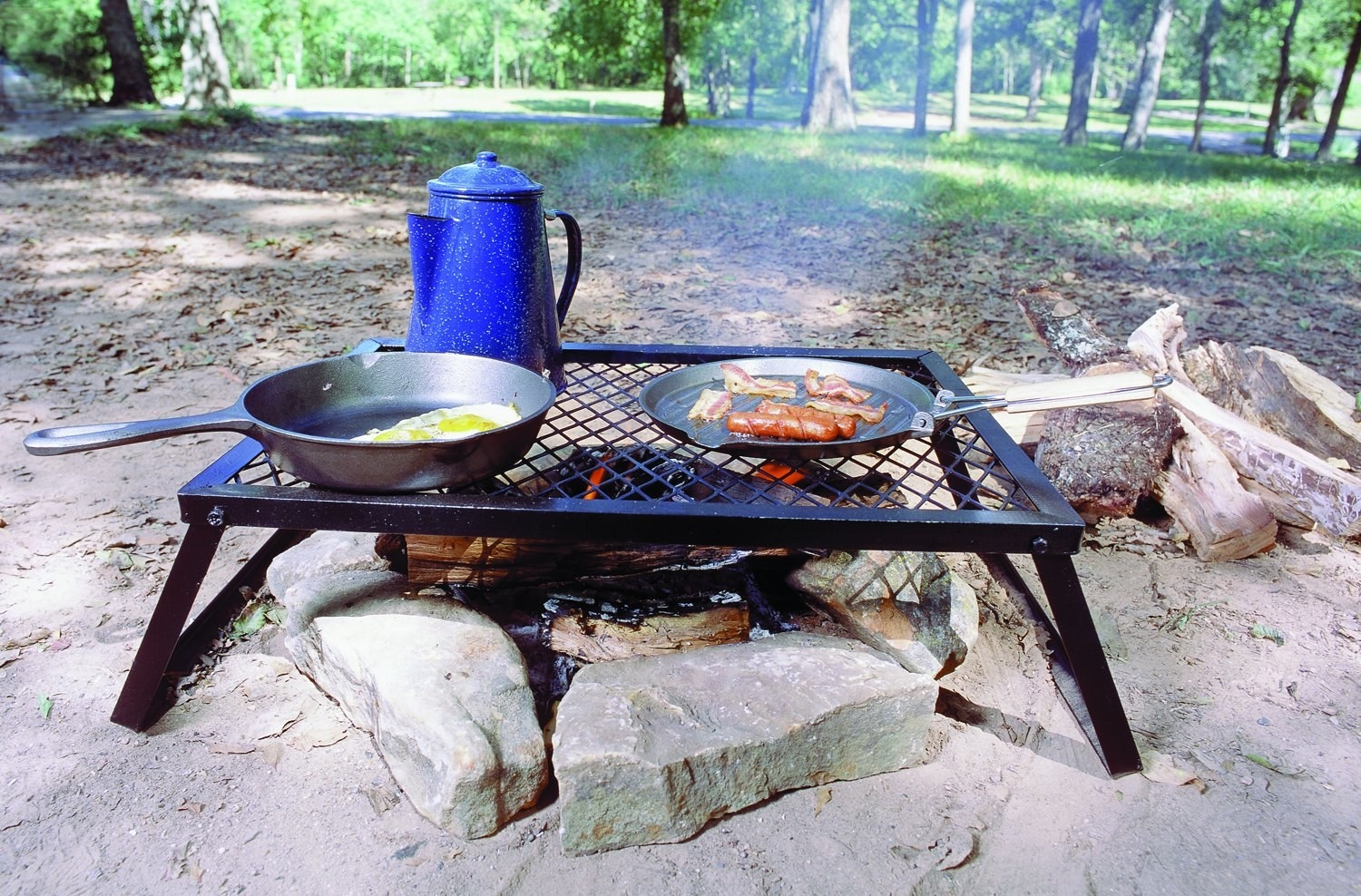 metal grate over campfire with two pans and a coffee percolator on top