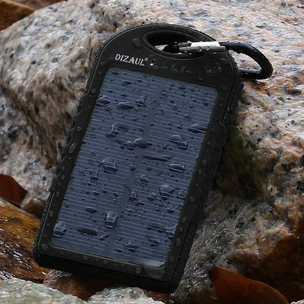 solar power bank with droplets of water on it and carabeener attached