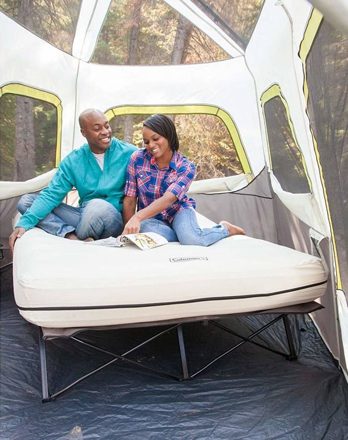 Two models sitting on a queen-size inflatable mattress on a cot inside a tall tent