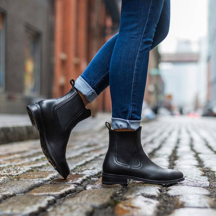 Model wearing black Chelsea boots with a half-inch heel, rounded toe, elastic panel on either side