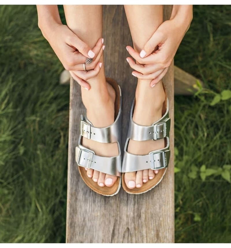 Model wearing Birkenstock footbed sandal with two side buckles across the top in metallic silver
