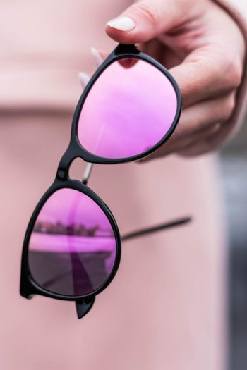 A hand holding black-framed sunglasses with mirrored pink lenses