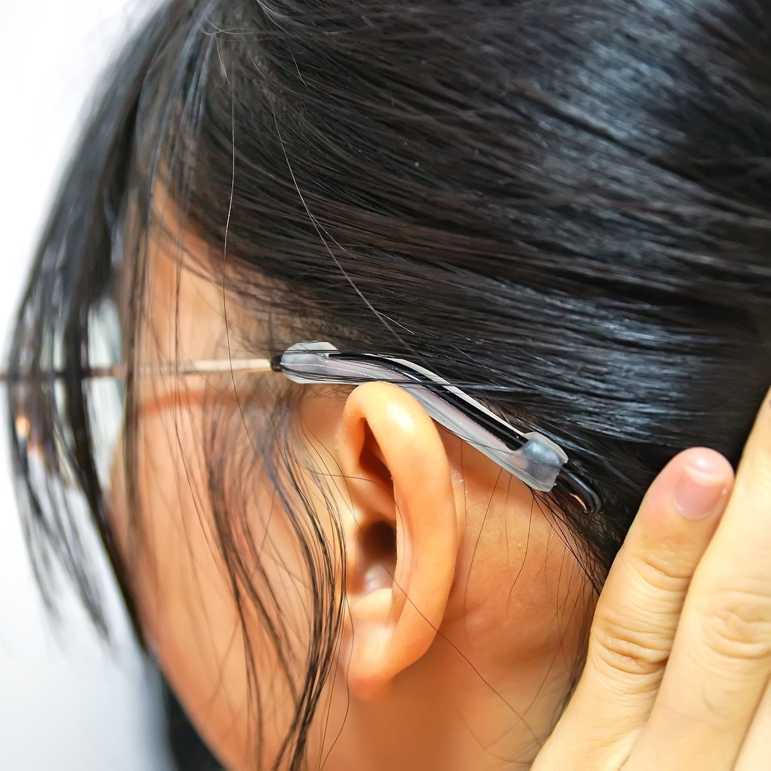 A model showing the glasses resting with the silicone cover on the back of their ear