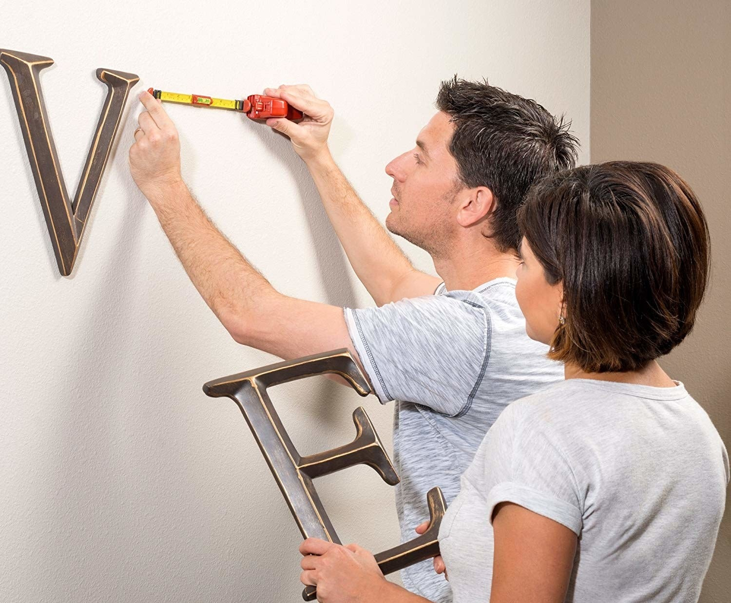 A person using the tool to hang a piece of wall art