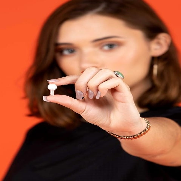 model holding tiny earplug between their thumb and forefinger