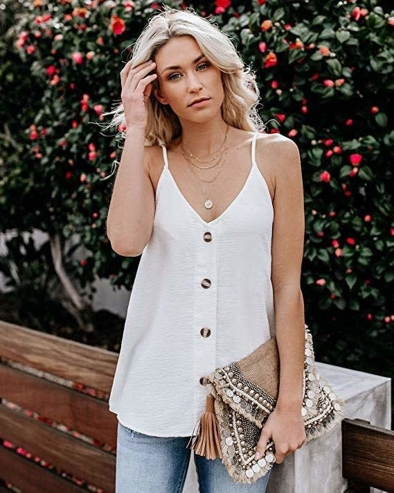 Model wearing the white flowy tank in white with large buttons down the front