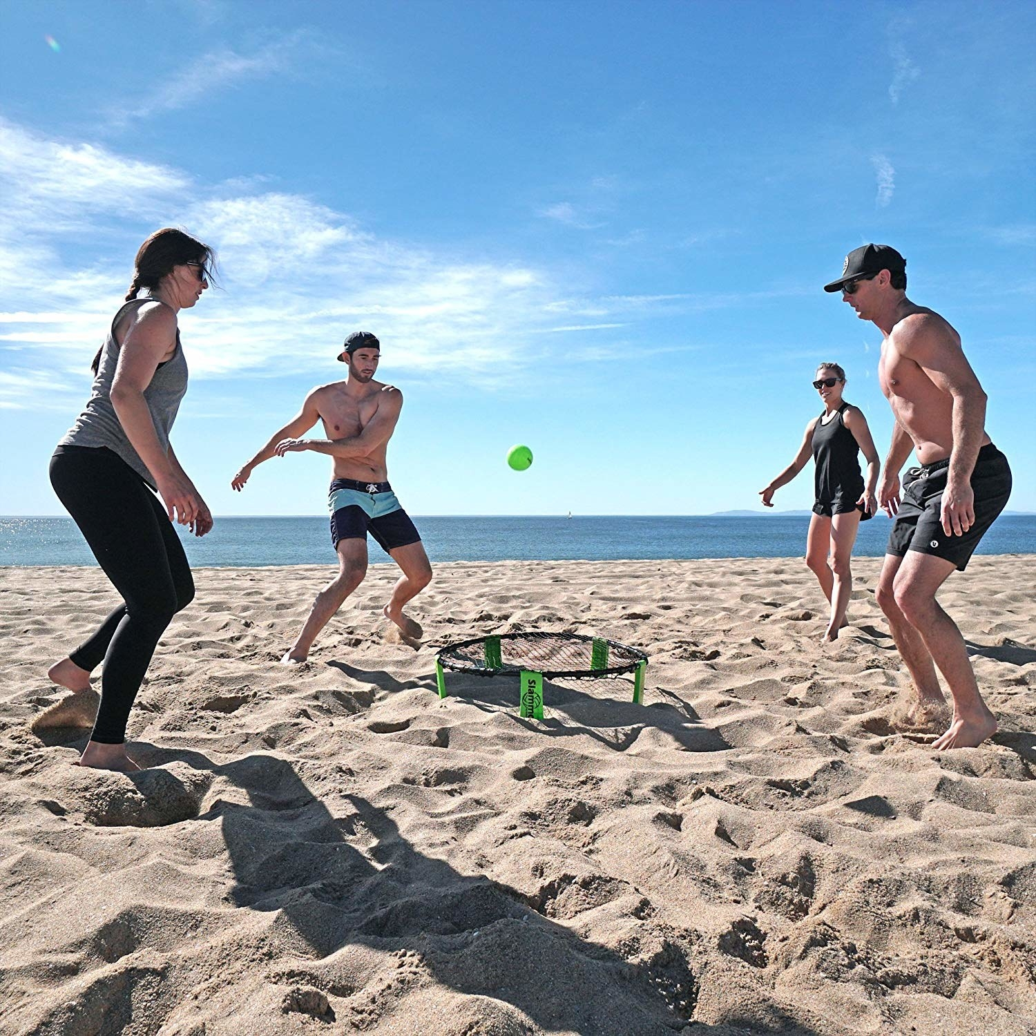 group of people standing around a slammo game at the beach
