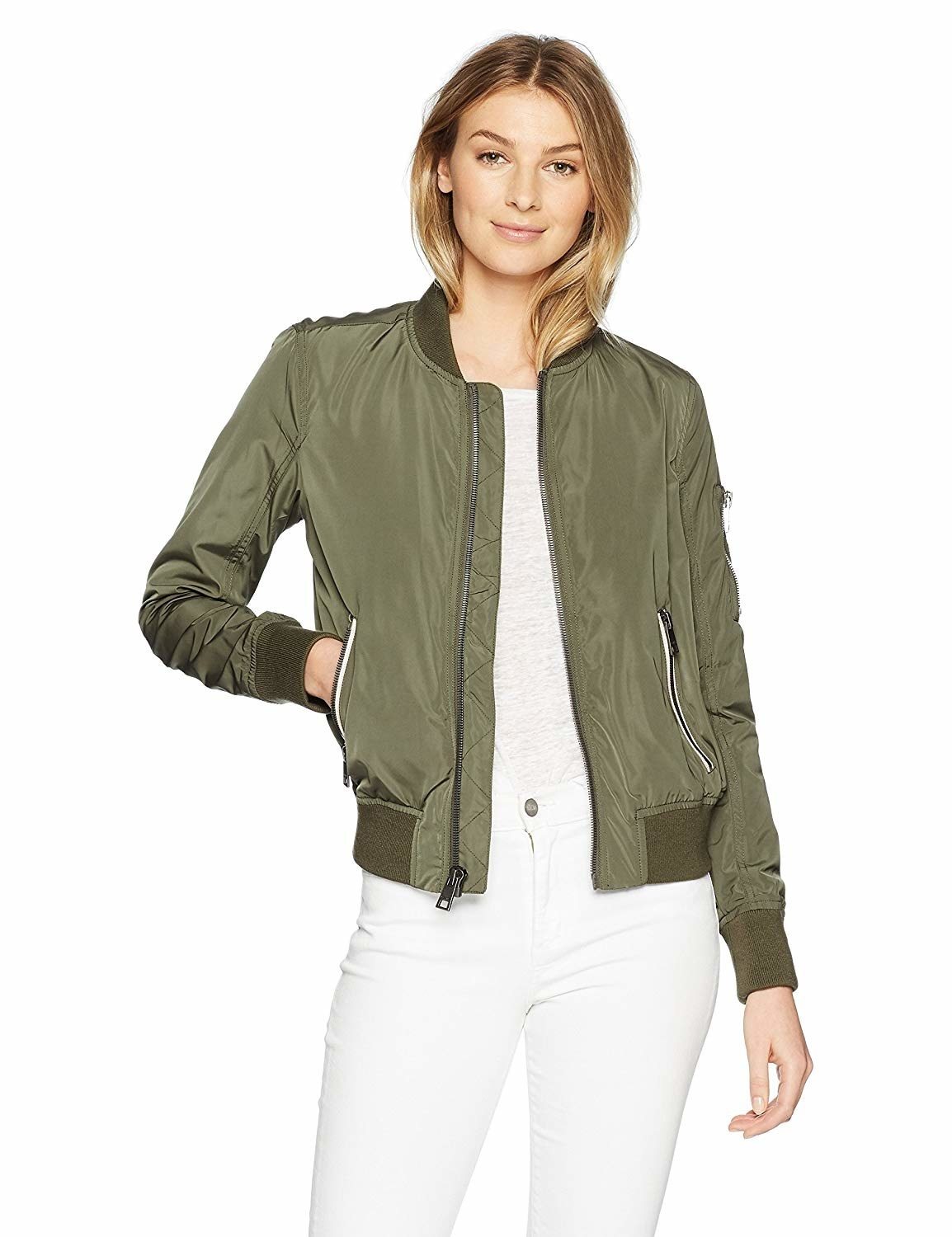 Model wearing bomber jacket with contrast zippers on side pockets and elastic around the neck, sleeves, and waist