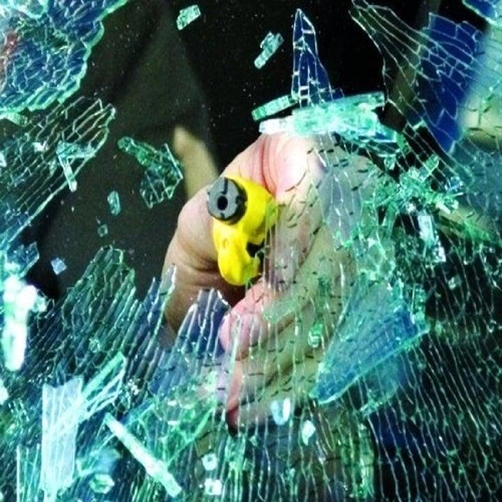 Model using tool to break car window