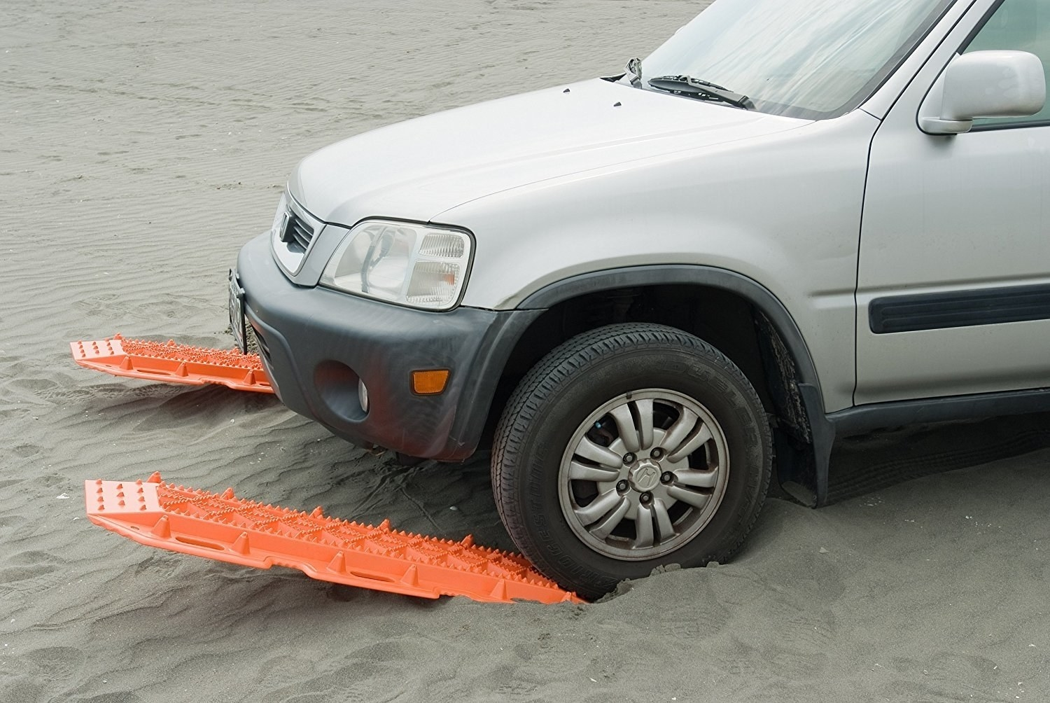 A car using the two bright orange escape trap to get out of being stuck in the sand