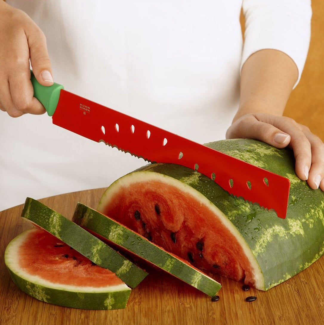 A model slices watermelon with the green-handled, red-bladed serrated knife