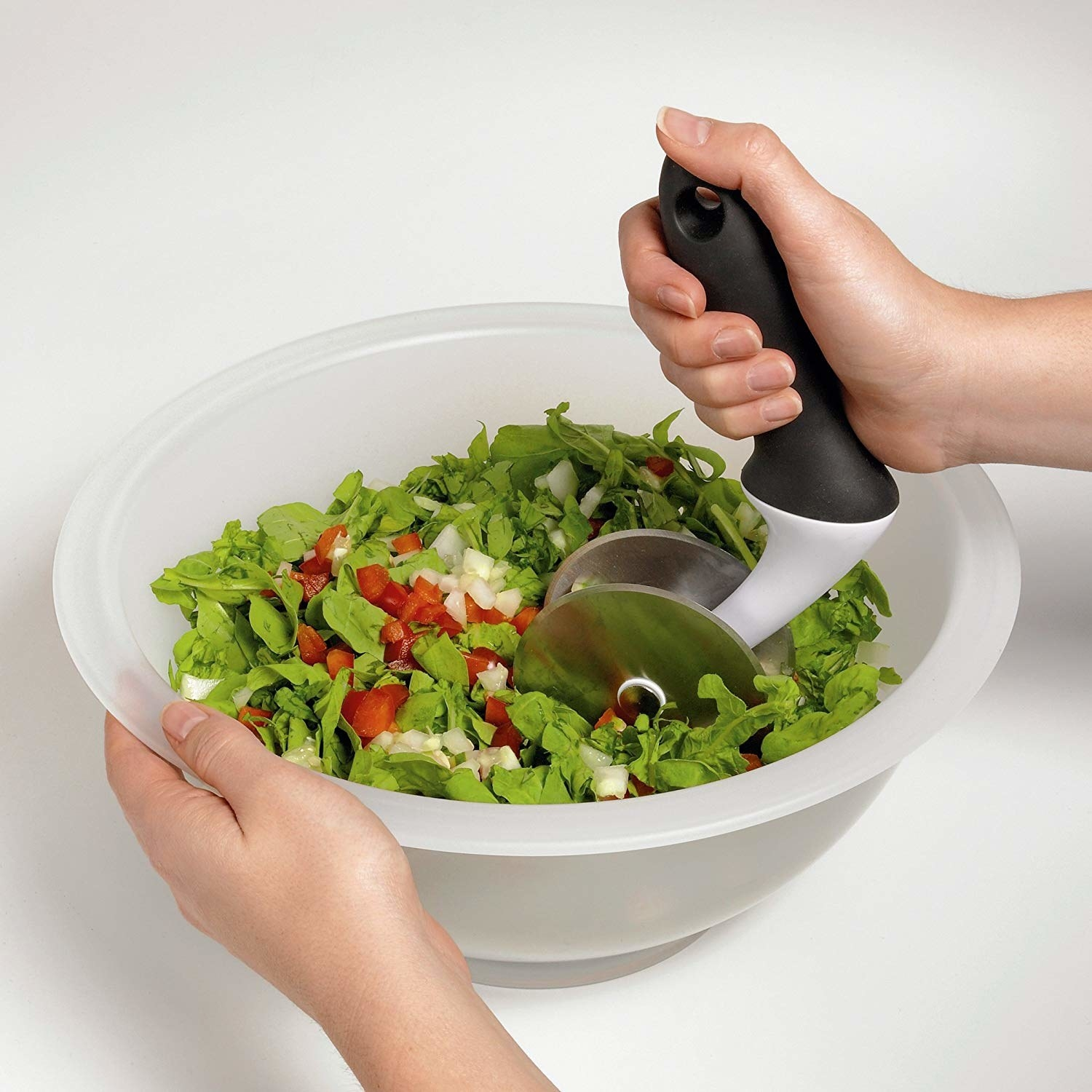 Hands rolling the double-pizza cutter-esque chopper through a bowl of greens and veggies