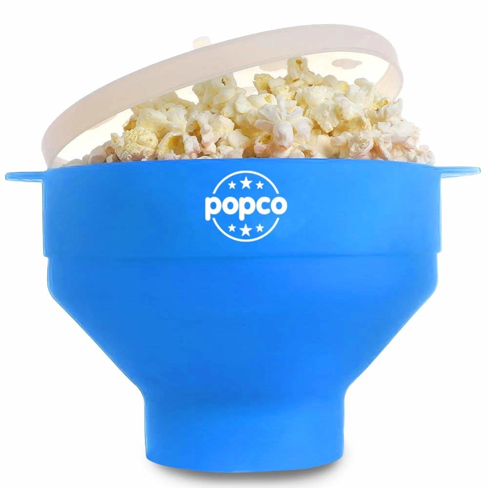 The blue silicone popper with popcorn in it and lid