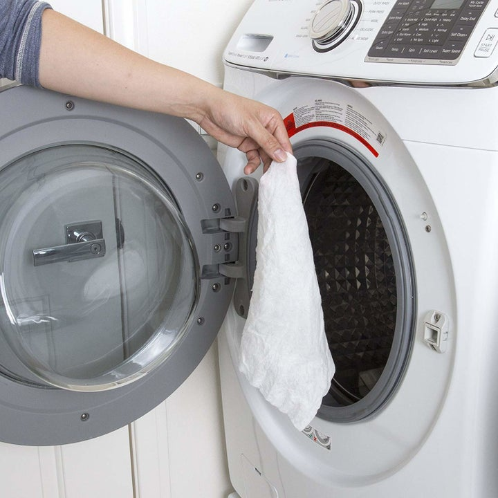 Hand putting the towel in a washing machine