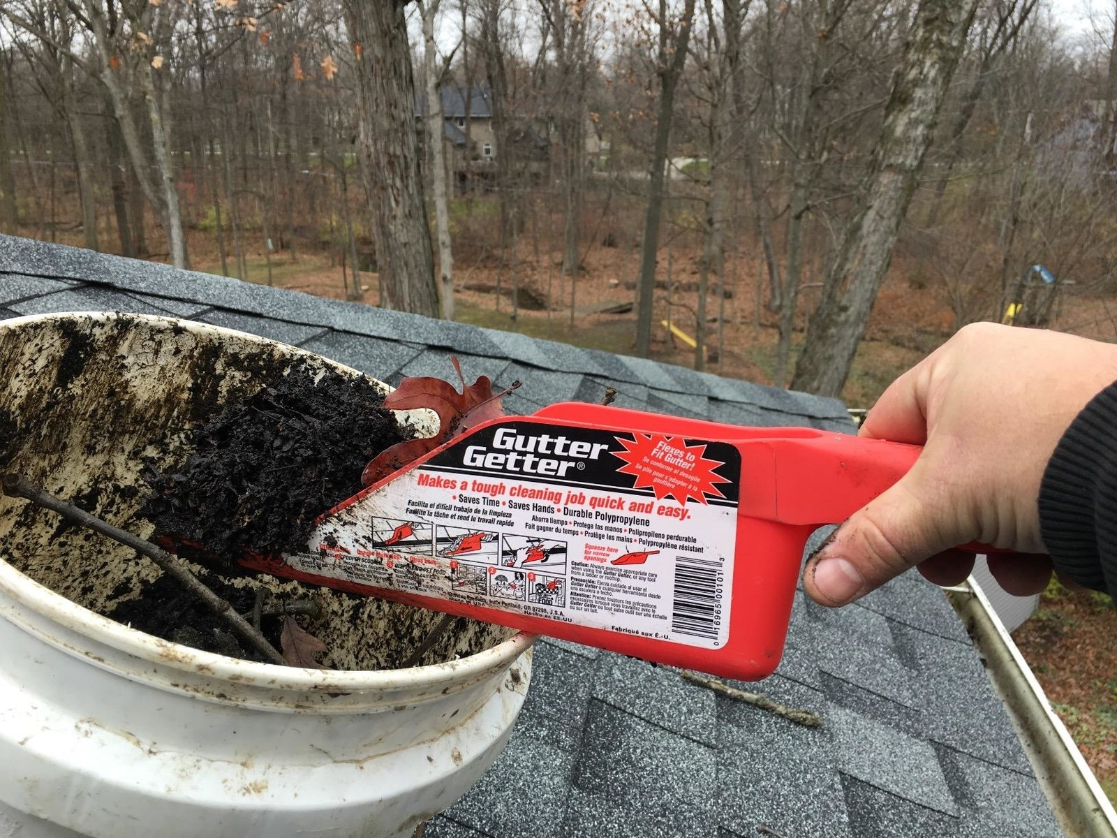 A reviewer on their roof, dumping gunk from their gutter in a bucket