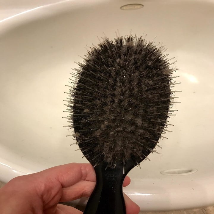 Before: a reviewer's very dirty hairbrush that looks like it has a black base