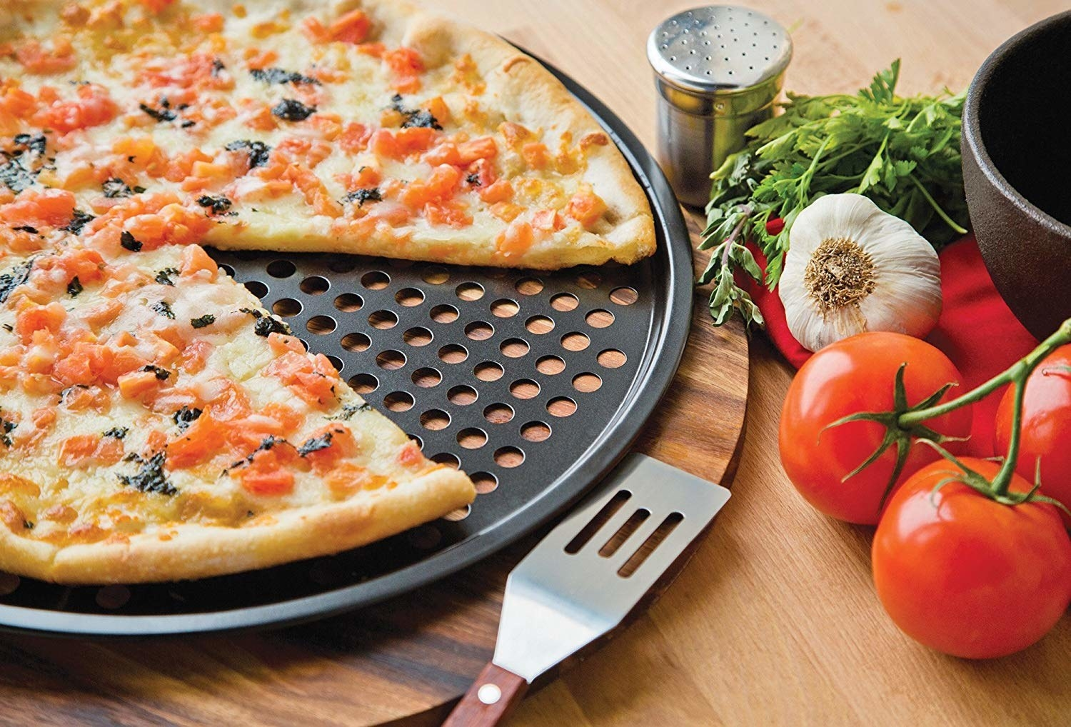 A thin-crust pizza on the round pan with holes in it