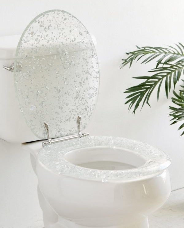 A transparent plastic toilet seat and lid with metallic silver flakes throughout