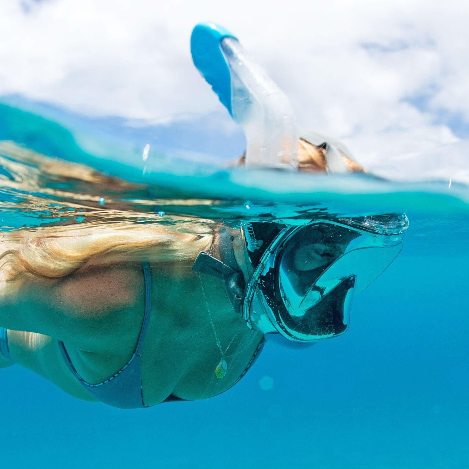 model wearing a full face snorkel mask while swimming in the ocean