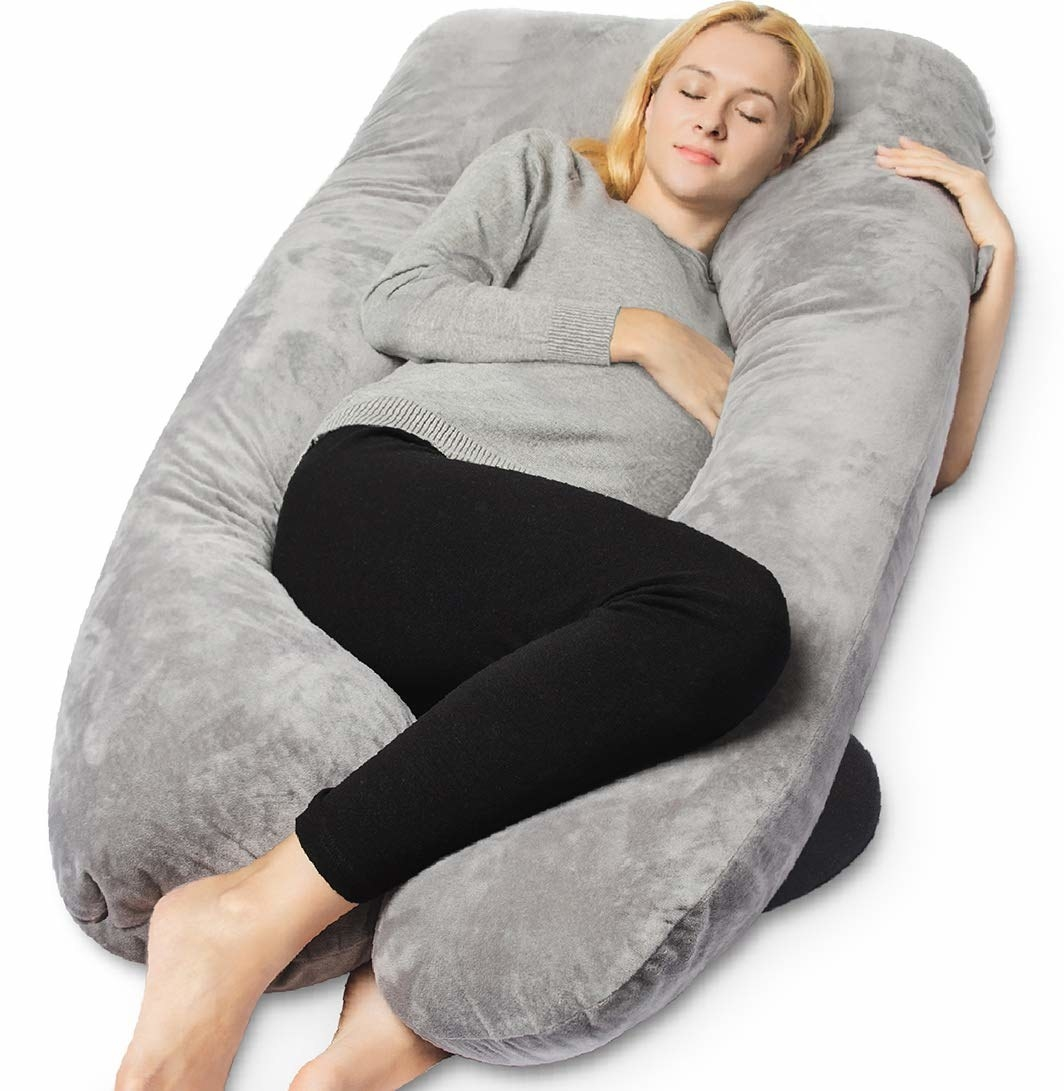 models cuddles with U-shaped body pillow