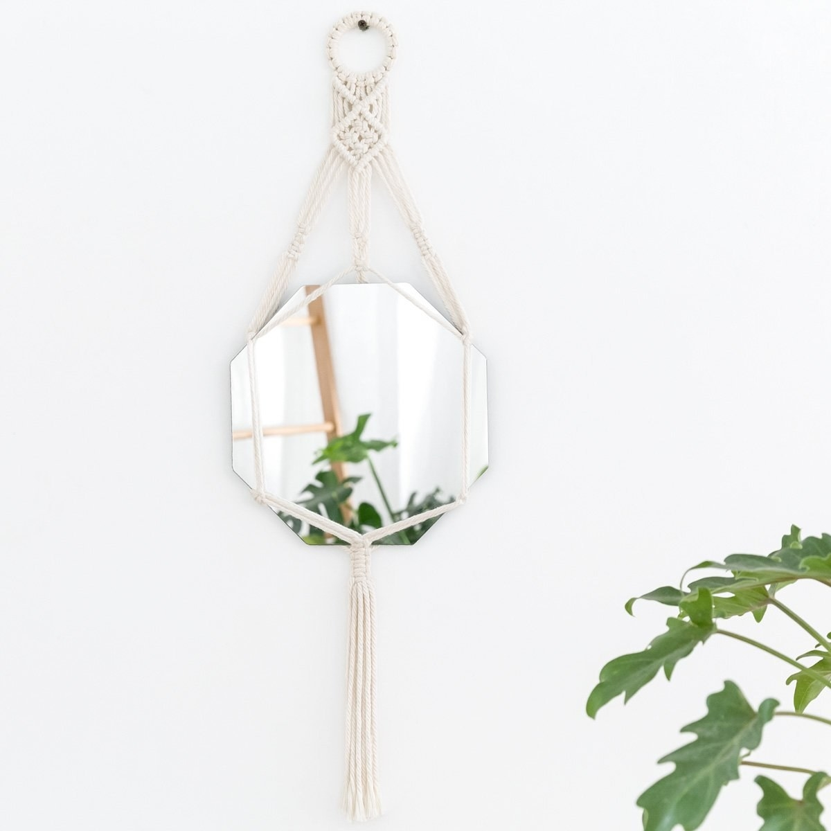The macrame wall mirror hanging on a wall.