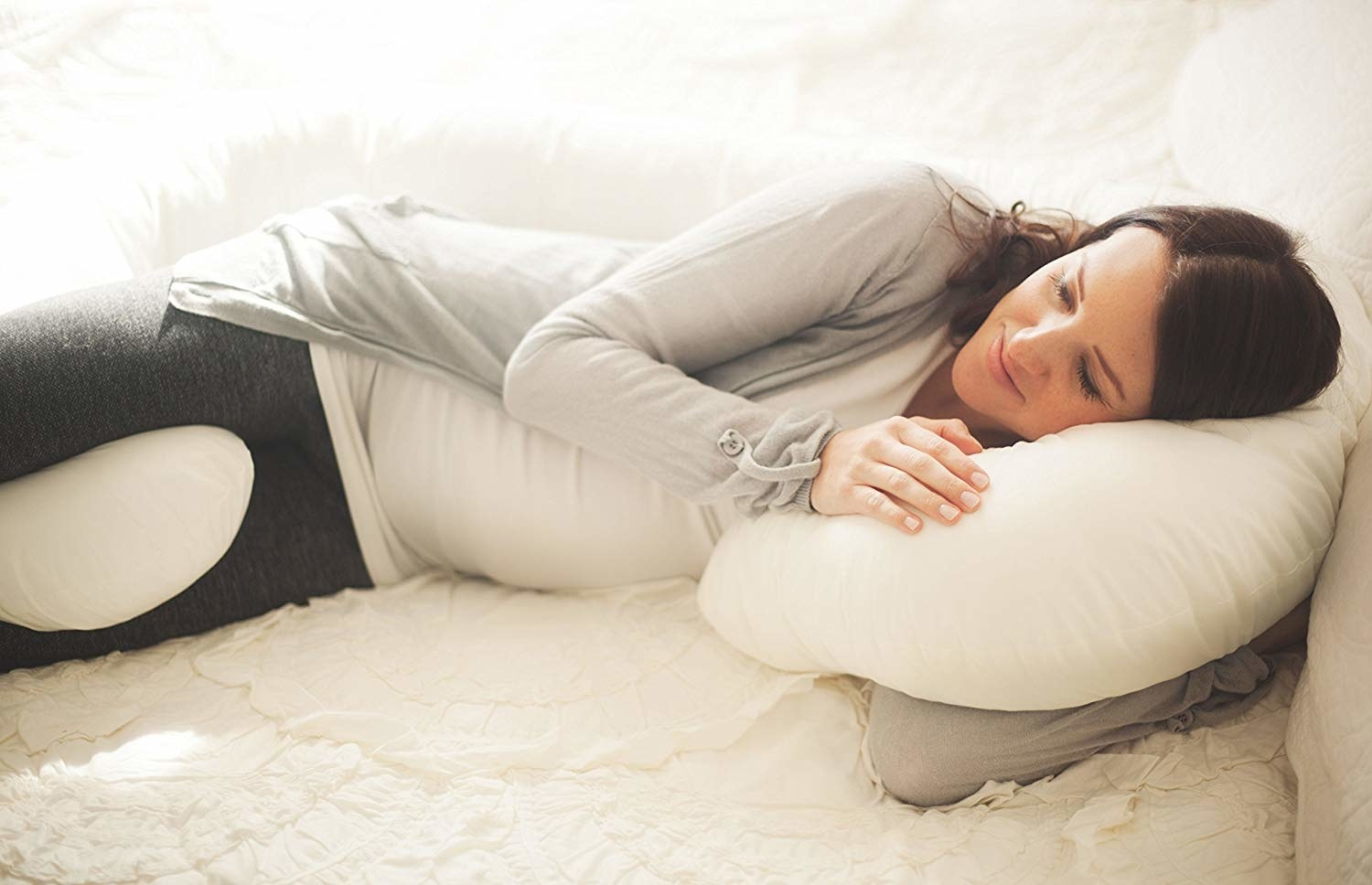 model snuggling with c-shaped pillow that supports under head and between thighs