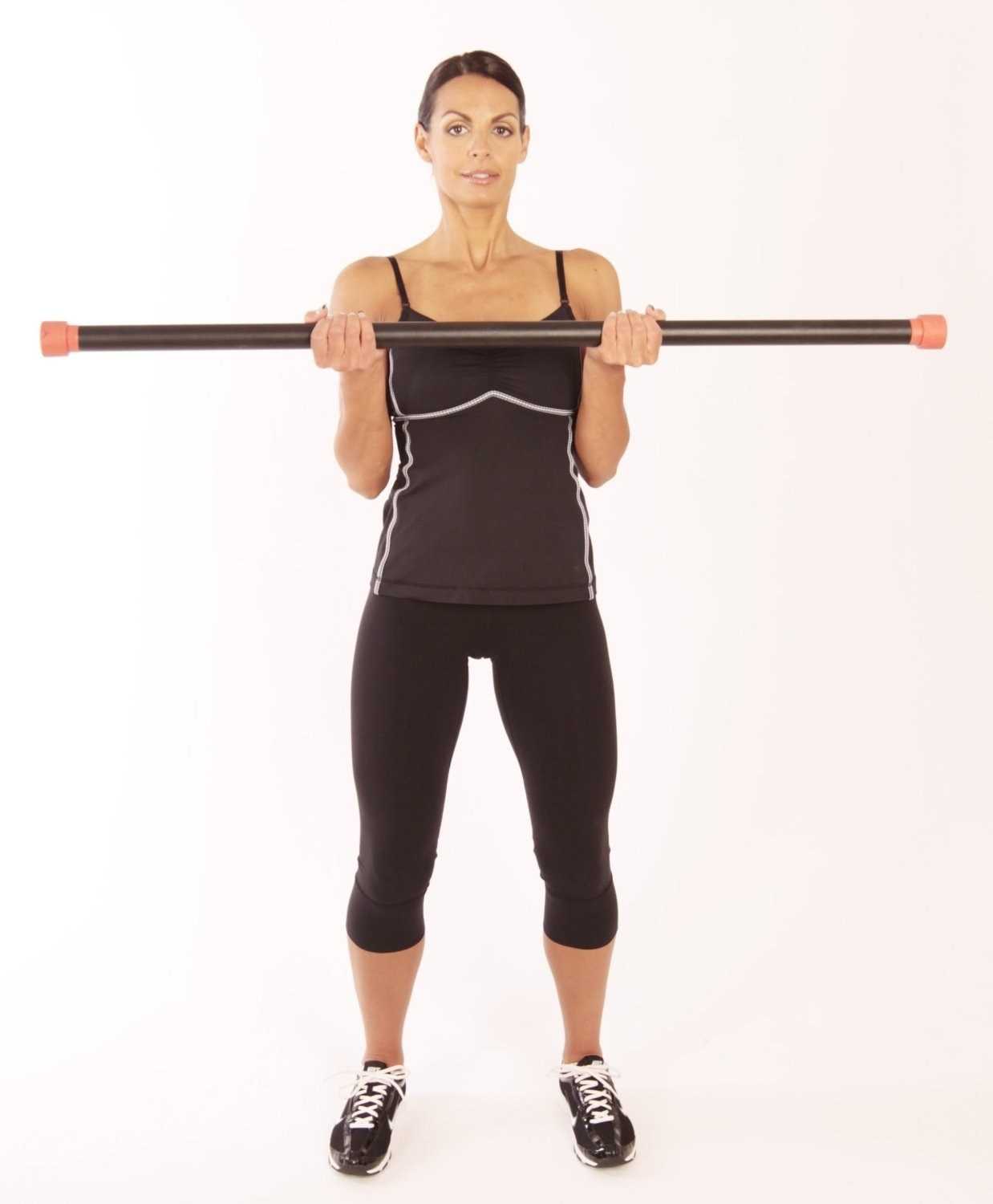 A person lifting the bar, about as long as their wingspan, to their chest while standing