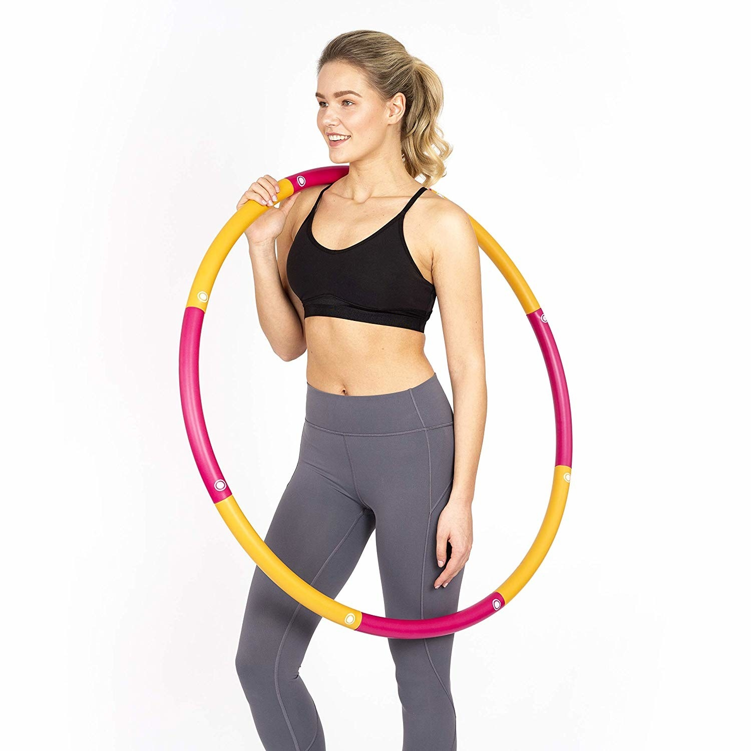 Person in workout clothes holding weighted hoola hoop across shoulder