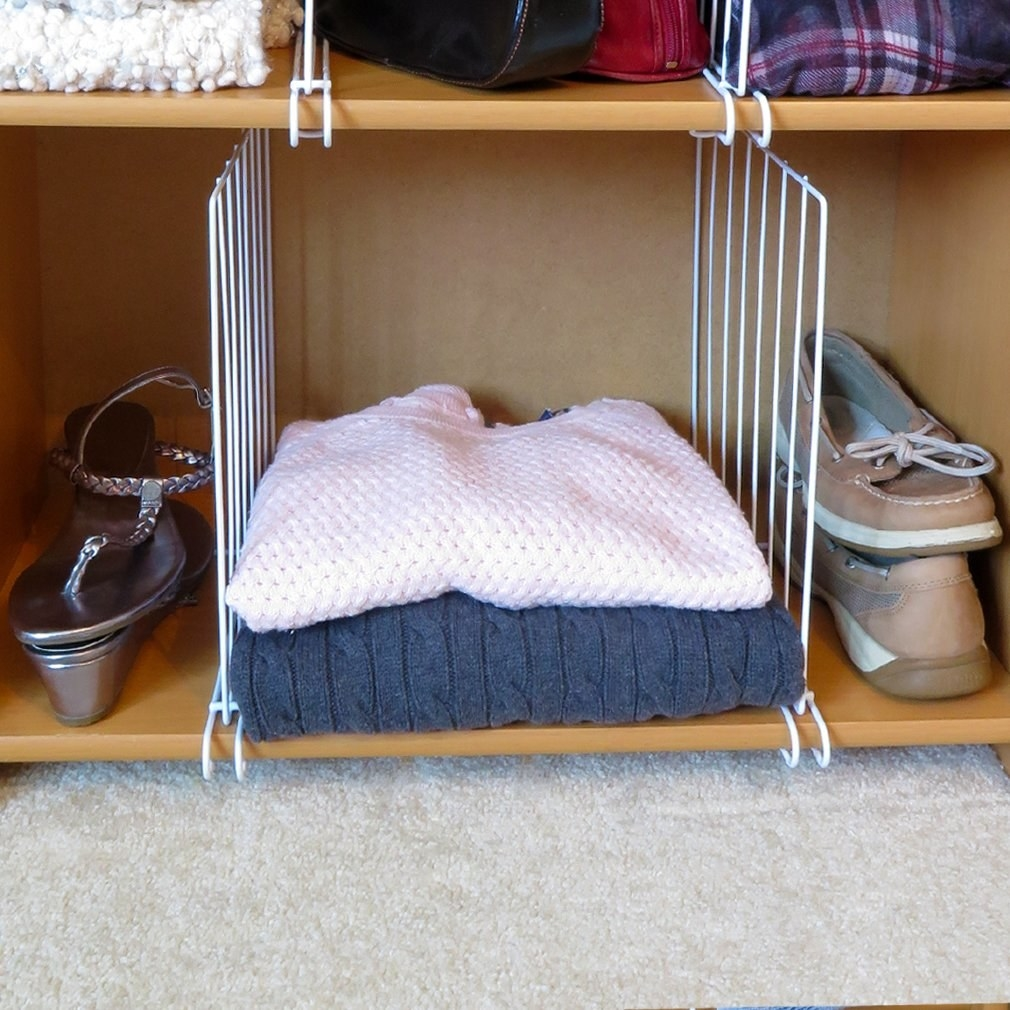 Two white wire dividers in a closet with shoes on either side and sweaters stacked in the middle.
