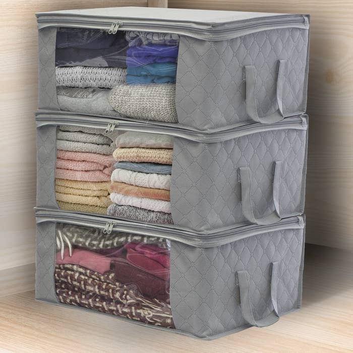 Three grey storage bags with clear panels on the side and handles on the front sitting on top of each other full of blankets and sweaters